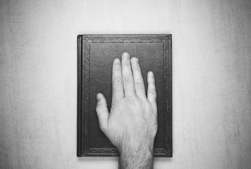 mans hand on the book, the oath on the Bible. top view closeup. black and white photo