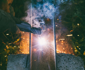 working man welder burns through an electrode hole in a steel channel in the evening, the view from the top