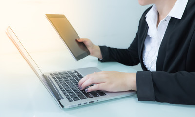 Business woman working on table with notebook and tablet