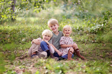 Family of Three Happy Young Children Posing Outside in Forest