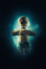 High contrast image of voodoo doll with smoke