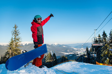 Full length shot of a snowboarder standing on the top of the mountains, showing thumb up, enjoying beautiful winter day copyspace vitality wellbeing sportsman sport seasonal recreation resort concept