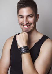 Portrait of young handsome man posing in front of camera with amazing big smile but with missing one tooth.