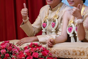 Happy time of bride and groom showing thump up sign in Thai traditional wedding ceremony.