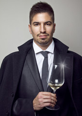 Portrait of young handsome man wearing nice suit with tie and white shirt. Looking straight at camera with bit of smile and in the hand holding glass with the wine. Cheers