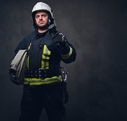 Firefighter in uniform holds fire hose.