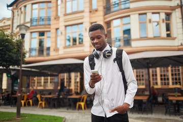 African man walking and looking at electronic map in smart phone.