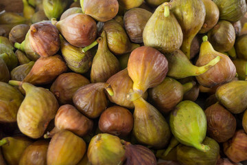 Brown and green figs in the market as a background