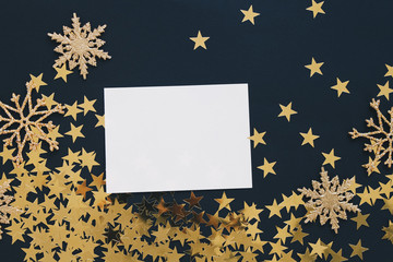 Christmas mock up greeting card on black background with glitter snowflakes ornaments gold stars confetti. Invitation, paper. Place for text flat lay