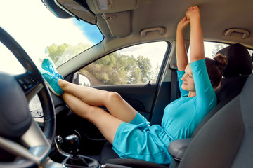 Girl in car sitting on front passenger seat with feet on car dashboard with hands up. Young woman relaxing with feet on dashboard. Freedom travel concept. Spending weekend in roadtrip