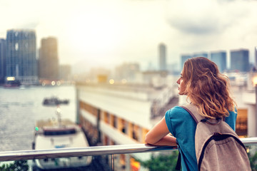 ourist woman on background of a big city with skyscrapers, looking at the sunset