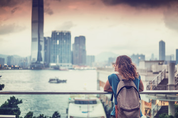 tourist woman on background of a big city with skyscrapers, looking at the sunset