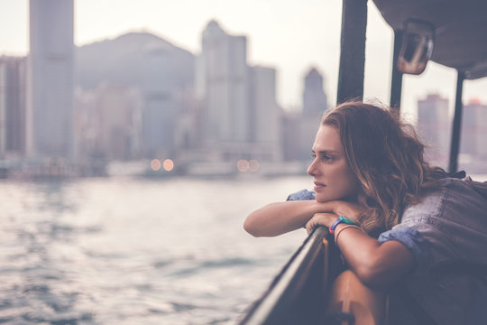 girl tourist on background of a big city with skyscrapers, looking at the sunset