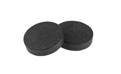 activated charcoal tablet isolated on white background
