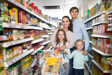 Adult smiling family with two daughters shopping
