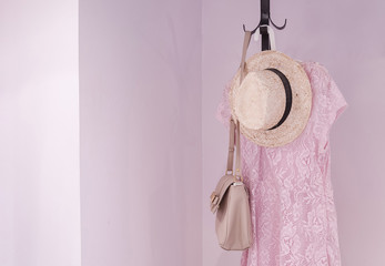 Coat rack with female accessories in bedroom, interior design for home.Clothes hanger.Rack for entrance hall with hangers, dresses, hat and bag