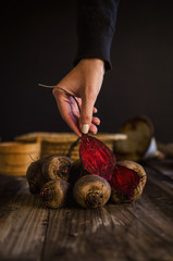 Female hand holding organic red beet on an old wooden table. Rustic style.