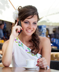 Young brunette woman is using mobile phone in a street cafe