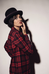 Attractive girl in red checkered shirt and hat bowler