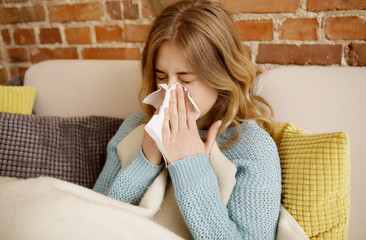Young woman with cold, flu or allergy blowing nose in paper tissue.
