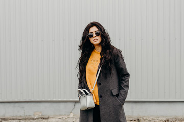 Portrait of stylish modern young curly woman in coat sunglasses. Trendy hipster. Urban life.