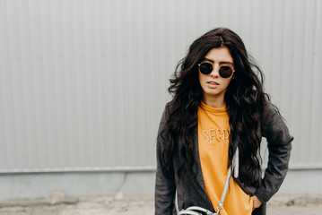 Portrait of stylish modern young curly woman in coat sunglasses. Close up portrait.