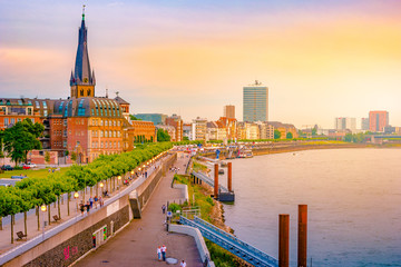 A view at the city skyline central Dusseldorf from the rhine river, Dusselfdorf Germany. Colorful panorama of german city at sunset.