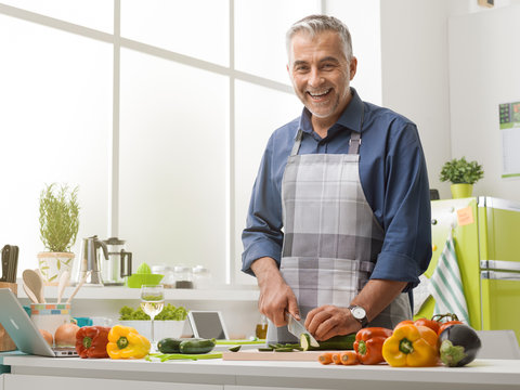 Happy man cooking in the kitchen