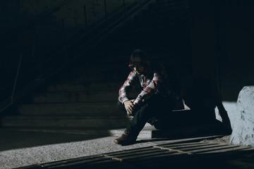 Man sits on the ground in darken tunnel