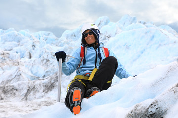 Woman climber resting on top of a glacier