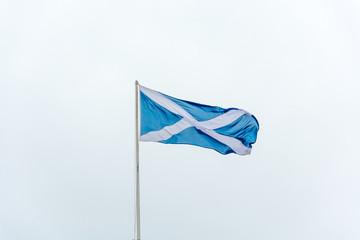 The flag of Scotland waving on a pole