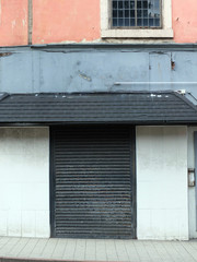 derelict abandoned commercial property in leeds england with black closed shutters and peeling cracked paint