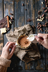 Female hands hold vintage mug of hot chocolate, decorated by nuts, caramel, spices, and pouring cream. Ingredients above over old wooden table. Flat lay with space. Dark rustic style