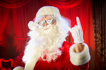 Santa Claus shows a hand a heavy rock symbol on a red background.