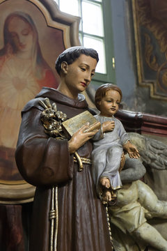 Saint Anthony of Padua holding baby Jesus statue with lily flower, church in Wroclaw