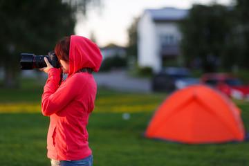 Girl photographer near of tent camp
