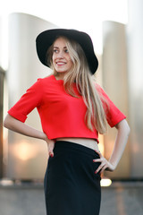 Happy young woman in red jacket and black hat