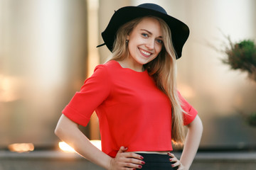 Happy young blonde in red jacket and black hat