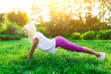 Picture of sports woman engaged in fitness on lawn