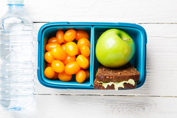 Picture of cherry tomato, apple, sandwich in lunchbox, bottle