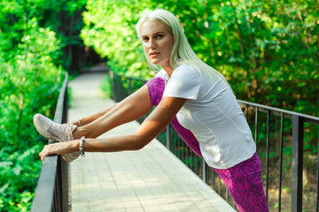 Photo of sports woman stretching on wooden bridge