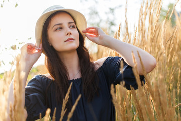 Image of young woman in hat in wheat field