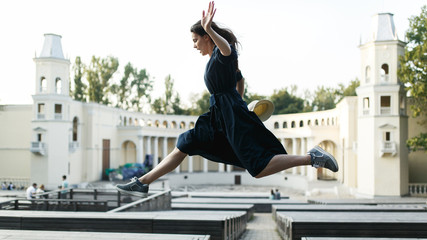 Girl in black dress jumping at city