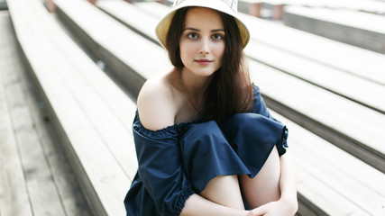 Photo of brunette in hat sitting on bench