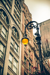 Vintage style illuminated streetlamp with New York City apartment buildings in the background.