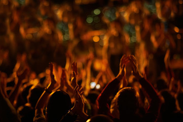 Audience with hands raised at a music festival and lights streaming down from above the stage.