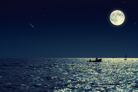Scenic view of small fishing boat in calm sea water at night and full moon