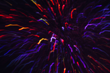 Abstract background of colorful lines in motion on black. Bokeh of defocused curves, blurred red, yellow and violet neon leds, festive backdrop of holidays and celebrations, fireworks and salute