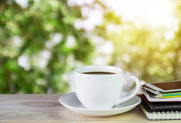 cup of coffee with blur image of abstract bokeh of green tree color