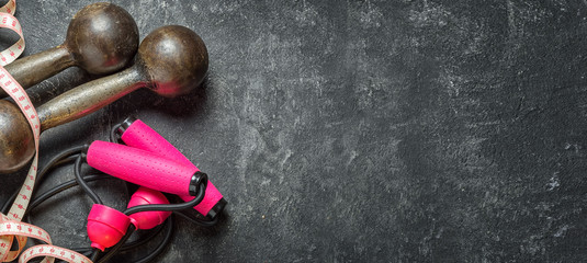 Bright sports concept. Sports equipment as dumbbells, expander with pink handles and centimeter tape on a dark black cement background, top view with a copy space.